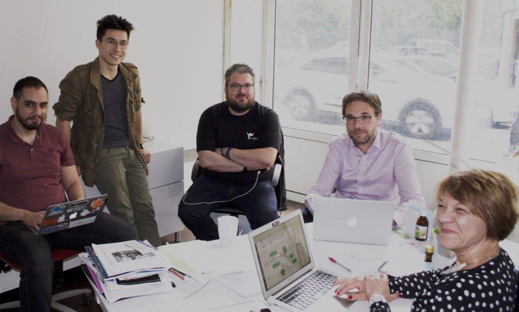 5 personnes autour d'un bureau en train de sourire à la caméra, trois sont sur leur pc portable. C'est l'équipe de dooloo
